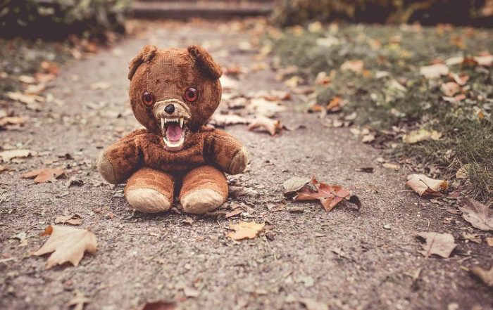 Worn teddy bear with comical fangs sitting in the middle of the sidewalk surrounded by autumn leaves.