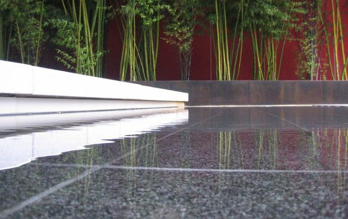 Placid, sleek pool of water in a Japanese zen garden reflecting modern architecture and bamboo shoots.