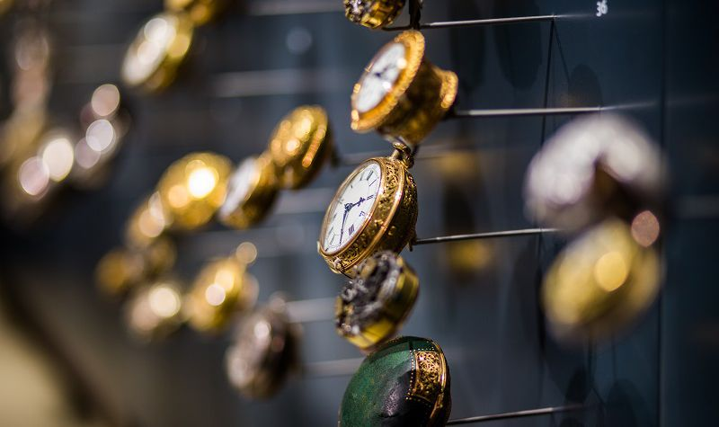 Multiple gold rimmed antique watches all set at different times.