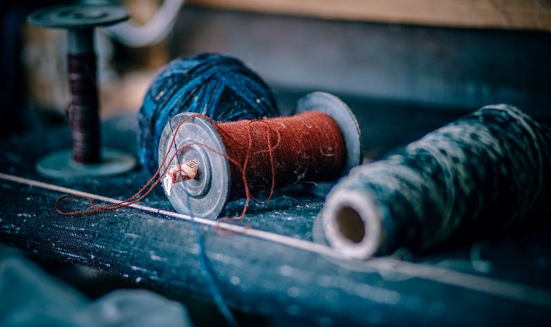 Antique spools of red and blue yarn slightly pulled and strewn about.