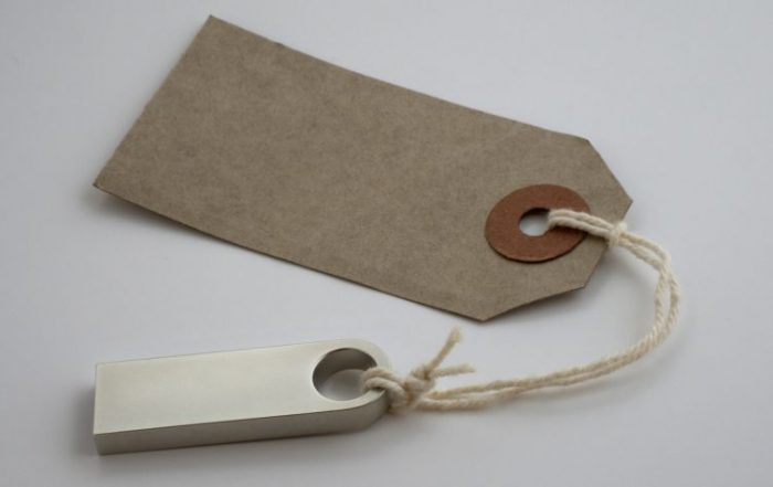 Blank brown paper tag label tied with yarn to a metal weight.