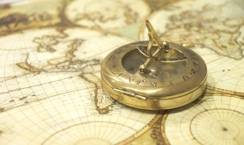 Gold nautical compass sitting on top of several antique maps.