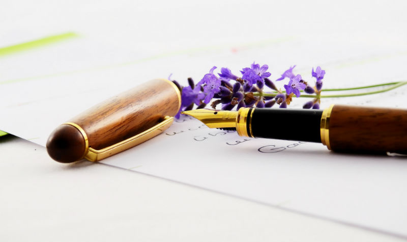 Lavender flower next to black and gold caligraphy pen sitting on a blank piece of white paper.
