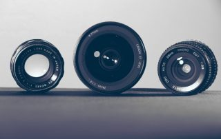 Three different types of camera photo lenses lined up from left to right against a white background.