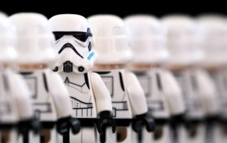 A long line of Lego Stormtroopers in a forward-facing row with one of them facing backwards.