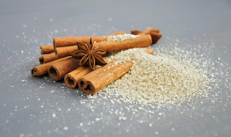Cinnamon sticks stacked on top of each other with star anis spices.
