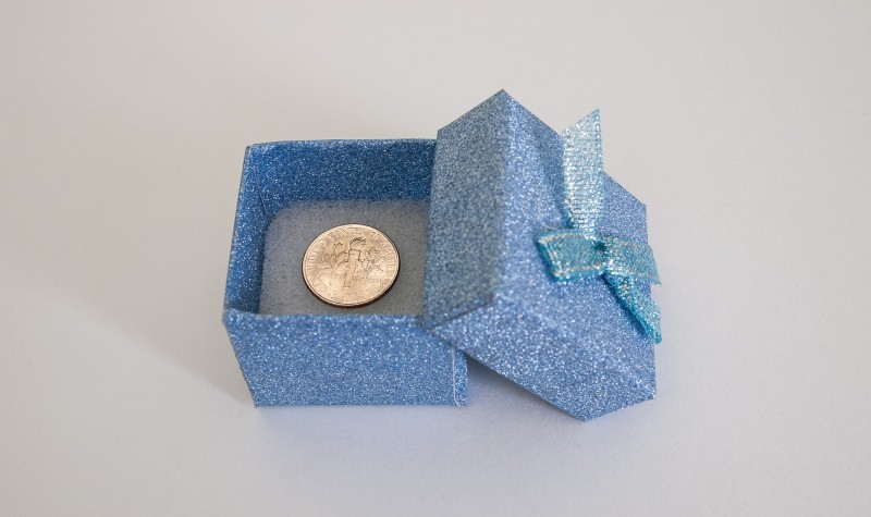 Small, baby blue gift box with the lid askew revealing a single, shiny new dime in the box.