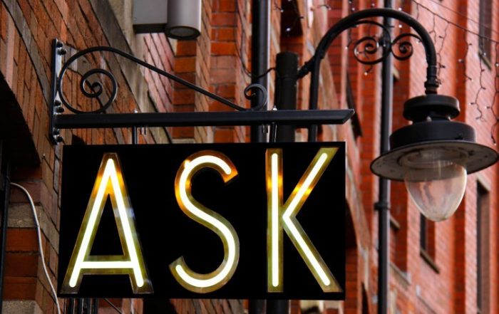 Black wrought iron light post sign with white letting that says ASK.