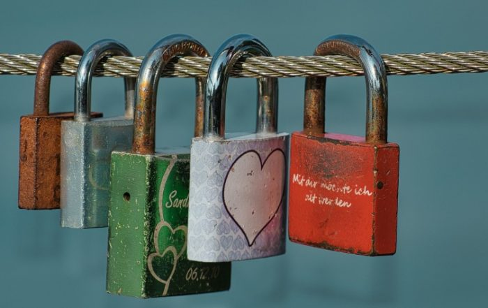 Five padlocks of different sizes and colors locked and strewn along a silver cable.