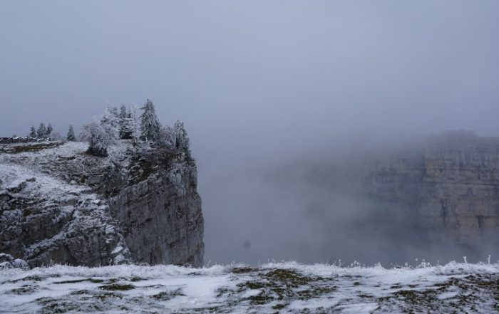 The Creux du van mountains in Switzerland showing a cliff drop off with fog in the distance.