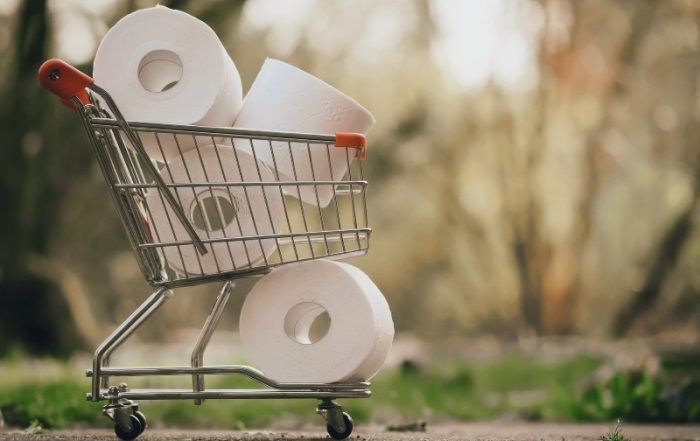 Metal shopping cart with red plastic handles packed with rolls of white toilet paper.